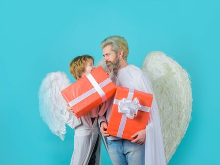 Happy father in angel costume with little son angel holds present. Valentines angels with gift box. Cute angel. Valentines day. Father and son Angels. Father's day. Little cupid boy gives father gift
