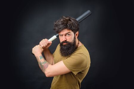 Sporty man in t-shirt. Ready to swing. Sport, training, health. Power. Energy concept. Bearded man with baseball bat. Baseball player with baseball bat. Sports and baseball training. Sport equipment