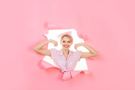 Fitness girl. Woman showing off her biceps. Vintage strong pin up girl looking through hole in paper. Fitness, sport, exercising, training concept. Girl showing his power. Woman flexing her muscles 版權商用圖片
