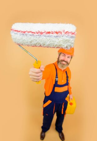 Painting concept. Bearded man in working clothes with paint roller. Bearded repairman in uniform hold paint roller. Repair man full height. Professional painter. Designer, builder, worker in hard hat 版權商用圖片
