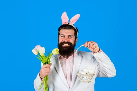 Happy easter. Holidays. Preparation for Easter. Easter Day. Happy bearded man with bunny ears hold basket with eggs. Man with bouquet tulips. Bunny man. Easter hunt. Bunny ears. Spring sale. Discount