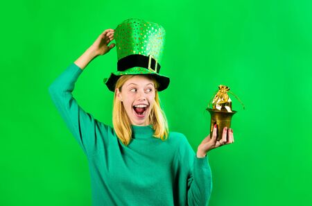 Saint Patrick's Day. Smiling girl in Leprechaun costume holds pot with gold. Leprechaun holds pot with gold. Green leprechaun. St Patrick's Day. Irish Traditions. Patrick's Day. Pot with gold. Gold