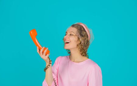Woman talking on retro phone. Girl talking on landline phone. Smiling woman in pink dress with telephone handset. Happy woman holds handset. Pretty woman talking at retro handset. Communication
