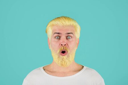 Blond hipster guy. Handsome man with stylish haircut. Bearded man with dyed blonde hair. Modern handsome man with blonde dyed hair. Eccentric man with dyed hair. Coloring of men's hair. Barbershop