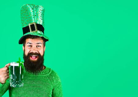 St. Patricks Day. Bearded man in leprechaun hat. Portrait of smiling man with green beer. Bearded leprechaun. Happy Irish leprechaun with black beard. Bearded man. Green background. Irish tradition.
