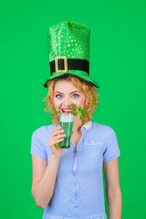 Beautiful girl in green leprechaun hat drinking green beer. Woman celebrating St Patrick's Day with beer. St Patrick's Day celebration. Patrick Day pub party. Saint Patricks day or october festival