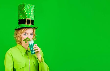 Saint Patrick's Day. Green top hat. St Patricks Day. Woman in top hat drink green beer. Leprechaun. Green beer. Green hat with clover. Irish Traditions. Pub. Woman drinking in pub. 版權商用圖片