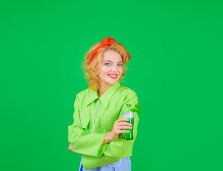 Woman drinking beer in pub. Saint Patrick's Day. St Patricks Day. Smiling woman holds glass with green beer. Green beer. Green beverage with clover. Irish Traditions. Pub. Green color, woman, clover