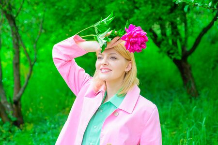 Peony flower. Beautiful girl with flower. Romantic girl holds peony flower in park. Woman in park. Spring. Smiling woman with peony bouquet. Fashion, cosmetic, perfume. Cute woman with pink flower