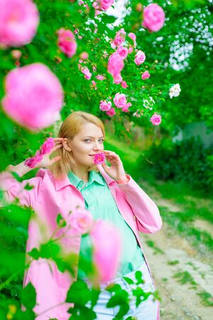 Woman in spring park. Beautiful woman near pink roses in garden. Beautiful girl in blooming garden. Elegant lady in blossom garden. Sensual woman at park with pink roses. Fashion, cosmetics, perfumes 版權商用圖片