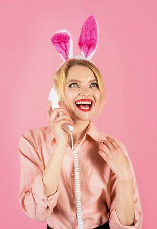 Happy Easter. Coloring egg. Hunting eggs. Communication. Girl with bunny ears talking on landline phone. Smiling girl talking on retro phone. Spring holiday. Easter celebration 版權商用圖片