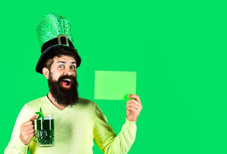 Saint Patrick's Day symbols. Bearded man in green hat holds green board. St Patrick's Day. Happy four leafed clover. Green hat with clover. Patricks Day green shamrock. Ireland tradition.