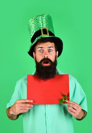 Saint Patricks Day. Bearded man in green top hat hold red board. Green hat with clover. Ireland tradition. Sale. Discount. Advertising. Saint Patrick's man hold blank poster. Happy four leafed clover 版權商用圖片