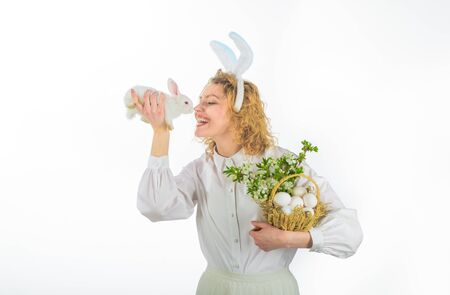 Easter day. Easter basket. Happy woman with white rabbit and basket. Girl holds little bunny. Beautiful girl with white rabbit. Easter basket. Easter Bunny. Cute furry rabbit 版權商用圖片