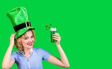 Irish Traditions. Saint Patrick's Day. St Patricks Day. Woman in top hat holds green beer. Leprechaun. Green beer. Irish Traditions. Pub. Woman drinking in Irish pub. Green top hat. Spring holidays