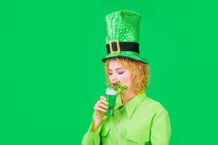 Woman celebrating St Patrick's Day with beer. Woman in top hat holds green beer. Leprechaun. Green beer. Irish Traditions. Woman drinking in Irish pub. Green top hat. Spring holidays. St Patricks Day