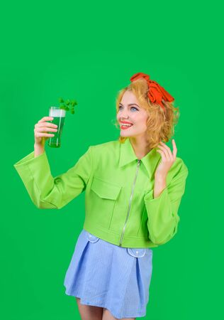 Traditions. Pub. Green color, woman, clover. Woman drinking beer in pub. Saint Patrick's Day. St Patricks Day. Smiling woman holds glass with green beer. Green beer. Green beverage with clover.