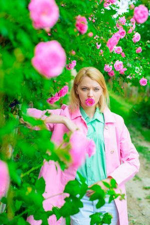 Elegant lady in blossom garden. Woman in spring park. Beautiful woman near pink roses in garden. Beautiful girl in blooming garden. Sensual woman at park with pink roses. Fashion, cosmetics, perfumes