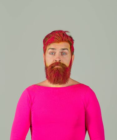 Sad man with dyed beard and hair. Bearded man with creative painting hair and hairstyle. Hipster with pink hair. Hairstyle. Hairstylist. Advertising, barbershop concept. Bearded man with colored hair