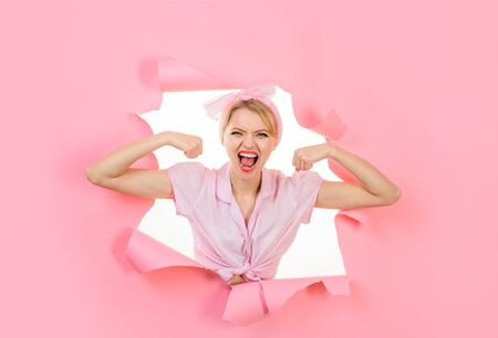 Woman flexing her muscles. Fitness girl. Vintage strong pin up girl looking through hole in paper. Fitness, sport, exercising, training concept. Girl showing his power. Woman showing off her biceps 版權商用圖片