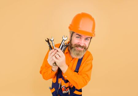 Business, building, industry, technology. Repairment tools. Wrenches. Spanner. Portrait of mechanical worker. Man builder. Builder with construction helmet. Hard hat