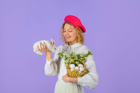 Happy Easter day. Basket with eggs. Easter bunny rabbit. Girl in fashionable beret hold basket with eggs and small bunny. Easter egg. Tradition of Easter. Beret hat. Accessory for woman. French style