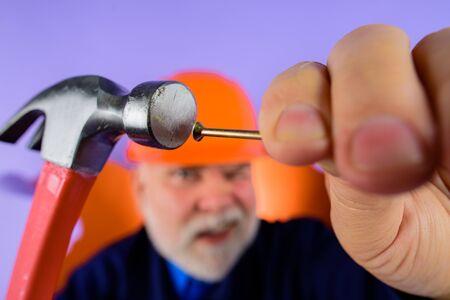 Repairment tools. Hammer and nails. Builder. Worker. Worker hammers nails. Repair man full height. Funny repairman. Crazy people. Funny people. Engineer. Hard hat