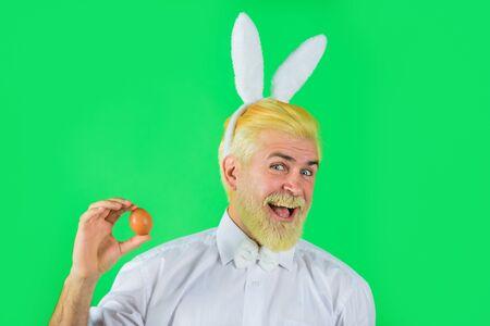 Happy Easter. Man in bunny ears holds Easter egg. Rabbit man. Man with rabbit ears hold Easter egg. Spring time. Easter eggs. Eggs hunt. Spring holidays. 版權商用圖片