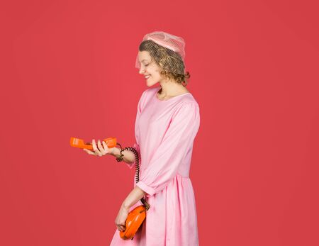 Woman talking on retro phone. Smiling woman in pink dress with telephone handset. Happy woman holds handset. Pretty woman talking at retro handset. Communication 版權商用圖片
