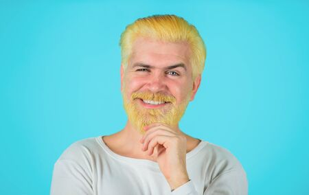 Barbershop. Eccentric man with dyed hair. Blond hipster guy. Handsome man with stylish haircut. Bearded man with dyed blonde hair. Modern handsome man with blonde dyed hair. Coloring of men's hair.