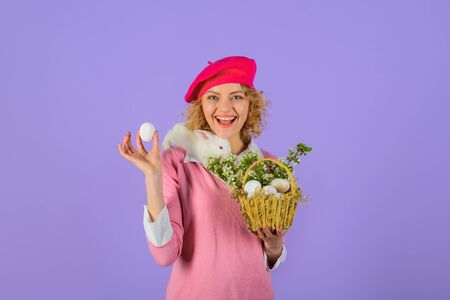 Girl in fashionable beret hold basket with eggs. Basket with eggs. Easter bunny rabbit. Small bunny on shoulders and Easter egg in hand. Beret hat. French style. Happy Easter day. Tradition of Easter