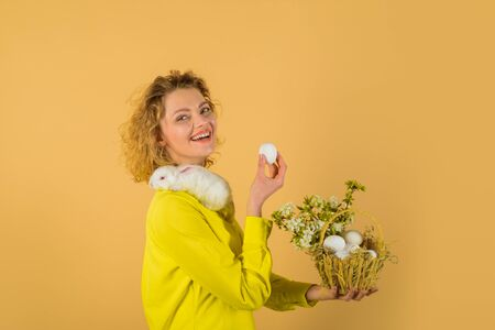 Basket with eggs. Eggs hunt. Easter egg. Bunny. Happy Easter day. Cute furry rabbit. Smiling woman holds basket with eggs and Easter bunny. Tradition of Easter. Religion symbol. Spring holiday
