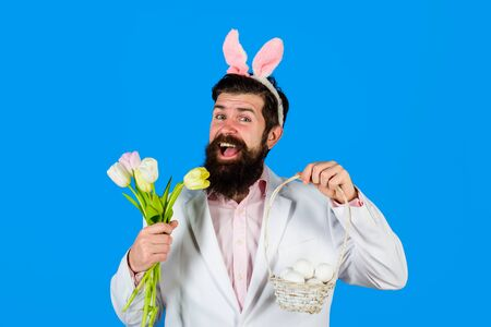 Easter Day. Preparation for Easter. Happy bearded man with bunny ears hold basket with eggs. Man with bouquet of tulips. Bunny man. Easter hunt. Bunny. Spring sale. Discount. Happy easter. Holidays