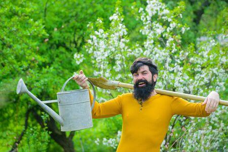 Spring. Work in garden. Bearded gardener with garden watering can and spade. Farm. Smiling man preparing to planting. Plants. Watering. Gardening. Gardener work. Farmer working in garden