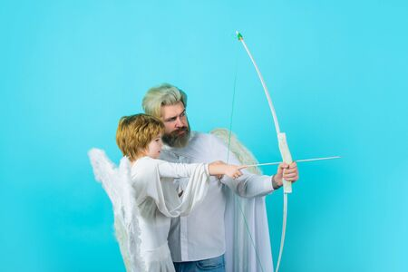 Little cupid boy and father. Happy father in angel costume and little son angel with bow and arrow. Christmas angels. Cute angel. Gorgeous kid. Valentines day. Father and son Angels. Father's day