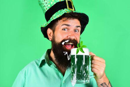 St. Patricks Day. Happy Irish leprechaun drinks green beer. Irish tradition. Bearded man in leprechaun hat. Portrait of smiling man with green beer. Bearded leprechaun. Bearded man. Green background