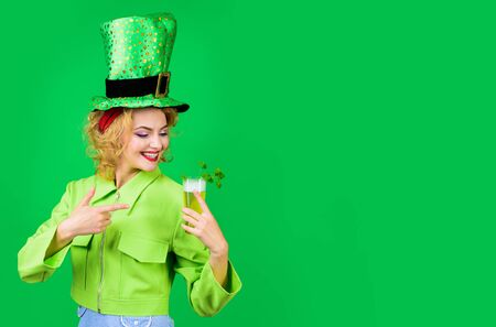 St Patricks Day. Green top hat. Saint Patrick's Day. Woman in top hat drink green beer. Leprechaun. Green beer. Green hat with clover. Irish Traditions. Pub. Woman drinking in pub. 版權商用圖片