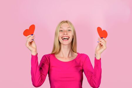 Valentine's Day. Smiling girl with red heart. Blonde woman with two paper hearts in hands. Happy girl on Valentine's day with hearts. Cute girl hold paper heart in hands 版權商用圖片
