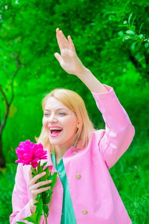 Elegant lady with peony flower. Romantic girl holds peony flower in park. Woman waving hand. Girl welcoming boyfriend. Relationships. Happy girl in spring park. Spring. Smiling woman with flower