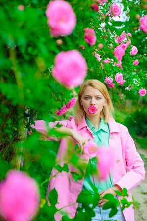 Sensual woman at park with pink roses. Fashion, cosmetics, perfumes. Woman in spring park. Beautiful woman near pink roses in garden. Beautiful girl in blooming garden. Elegant lady in blossom garden 版權商用圖片