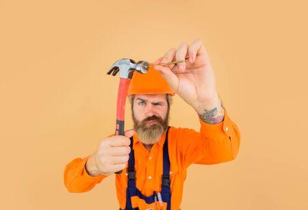 Hammer and nails. Builder. Worker. Worker hammers nails. Repair man full height. Funny repairman. Crazy people. Funny people. Engineer. Hard hat. Repairment tools 版權商用圖片