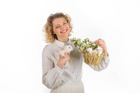 Spring holiday. Easter egg. Bunny. Happy Easter day. Cute furry rabbit. Smiling woman holds basket with eggs and Easter bunny rabbit. Tradition of Easter. Religion symbol. Basket with eggs. Eggs hunt