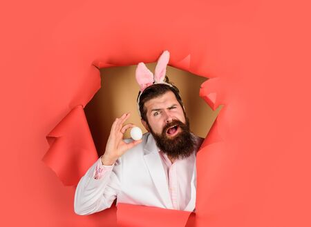Happy Easter! Through paper. Easter. Bearded man with bunny ears. Smiling man holds white egg. Bearded man through paper. Egg hunt. Easter. Bunny ears. Breaking paper. Sale. Discount. Advertising