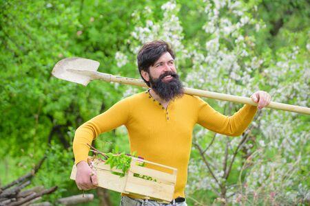 Gardening. Plants. Farm. Work in garden. Spring. Gardener with gardening shovel. Work in garden. Gardener work. Smiling man preparing to planting Standard-Bild