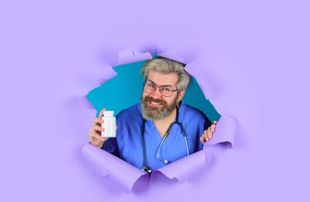 Pharmaceutical drug. Bearded doctor. Doctor with stethoscope holds pills. Through paper. Doctor with pills. Medicine. Nurse. Bottle of pills. Treatment pill. Healthcare. Hospital and pharmacy concept