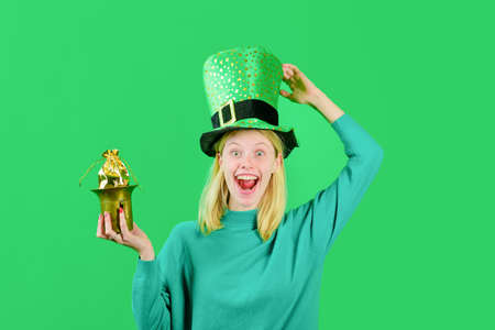 Saint Patrick's Day. Green top hat. Blonde girl in Leprechaun costume holds pot with gold. Leprechaun. Pot with gold. Green leprechaun. Green hat with clover. Traditions of Saint Patrick Day