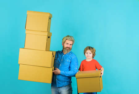 Moving, home and family concept. Father and son holds cardboard boxes. Father holds stack cardboard boxes and son helping him. Prepare for moving. Father and son with shipping boxes. Packaging things