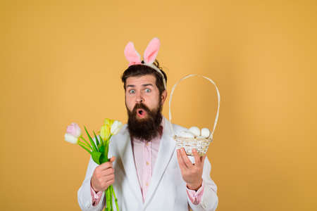 Easter celebration. Happy Easter. Surprised bearded man in suit hold basket of egg. Spring flowers. Bearded man. Eggs hunt. Rabbit costume. Preparing for Easter. Easter eggs. Holidays
