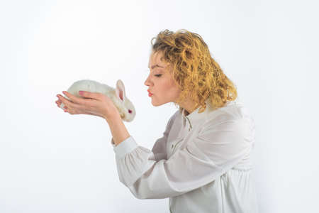Easter. Easter Bunny. Happy woman holds white rabbit. Girl with little bunny. Beautiful girl kisses white baby rabbit. Easter rabbit. Friendship with Easter Bunny. White furry rabbit Stok Fotoğraf - 162232060