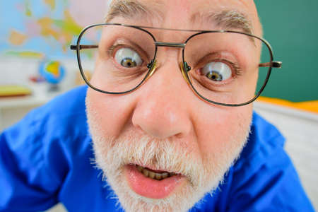 Surprised teacher in glasses. Teacher or professor working in classroom. Teachers day. Teacher prepares lessons in classroom. Learning, education, school concept. Male tutor in on lecture. Closeup Stok Fotoğraf